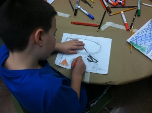A student sketches his idea for the puppet show.