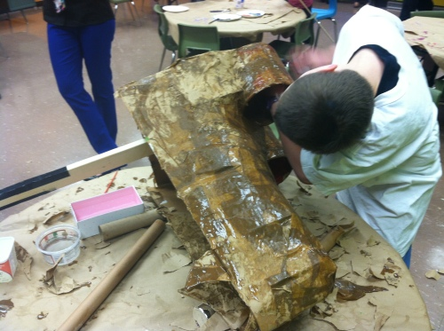 Creating a giant puppet with cardboard and papier mâché.