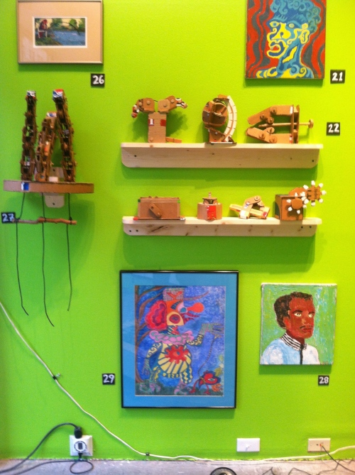 At top, robotic hand and other cardboard sculptures by Doug Hill.  At bottom, paintings by Steve Smith.