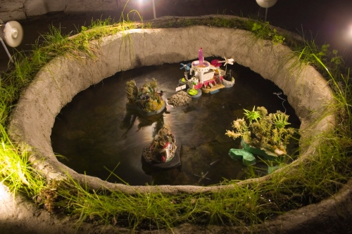 Earth pond.  A cement crater with miniature islands (Islands of Consumerism, Barren Wasteland, Extinction and Pristine Wilderness).  Live video feed of pond activity to Universe Room installation upstairs.