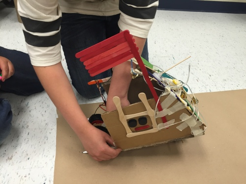As student setting a robotic vehicle to motion.