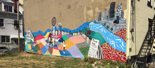 The completed mural spans the length of an apartment building.
