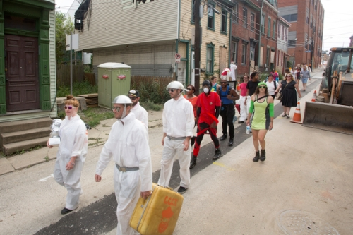Teams parade from the Neu Kirche Contemporary Art Center to Art Olympic Field, accompanied by Colonel Eagleburger's Highstepping Goodtime Band.