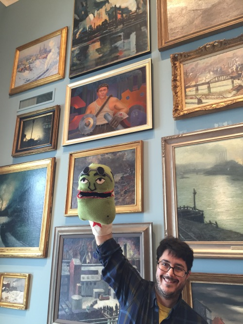 Mike Cuccaro with Mike Kessel puppet, under the Portrait of Mike Kessel.